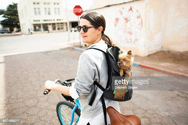 Woman cycling with small dog in backpack