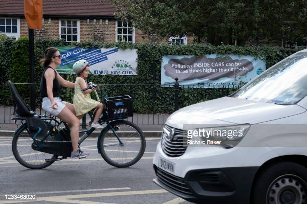 Woman cyclist carrying a child on her bike passes a pollution awareness banner that is attached to the railings of Dulwich Hamlet School, where...