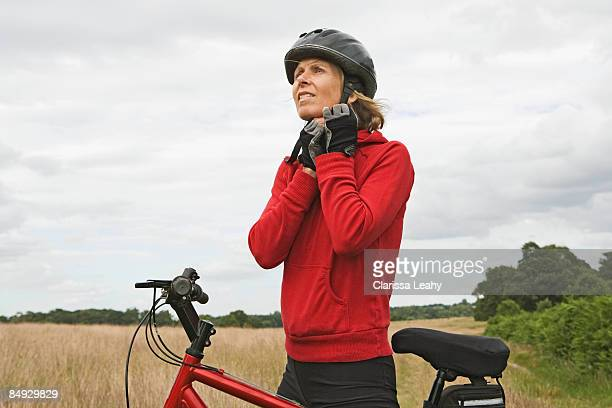 Woman cyclist doing up helmet