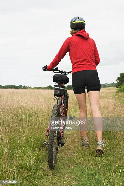 Woman cyclist pushing bicycle rear view