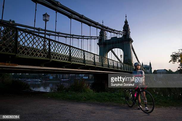 a woman cyclist with a racing bike at hammersmith bridge at dawn - fulham stock pictures, royalty-free photos & images