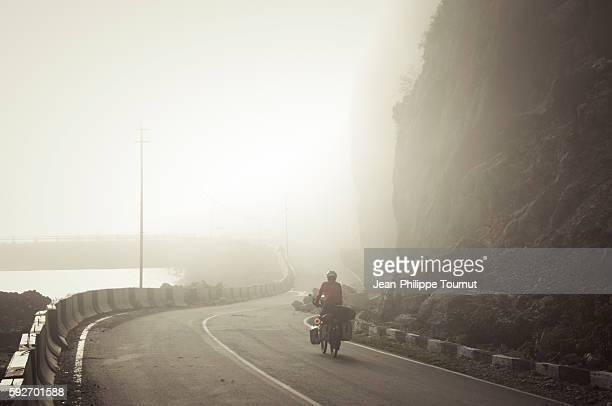 Woman cyclotourist cycling in the morning fog, Georgia, Eurasia