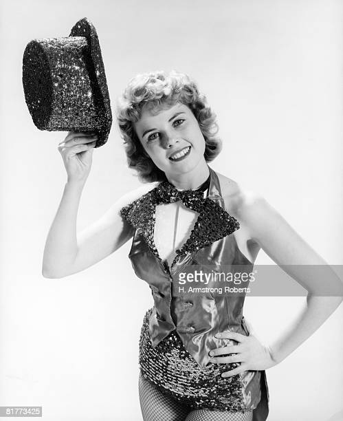 Woman Dancer In Satin Leotard Vest & Bow Tie With Hand On Hip Tipping Sequin Top Hat To Viewer Entertainment Broadway Show Performer