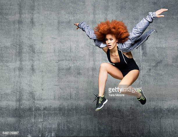 woman dancer jumping in air in urban studio - solo una donna giovane foto e immagini stock