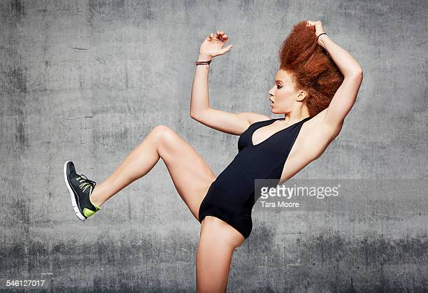 Woman dancer with leg in air in urban studio
