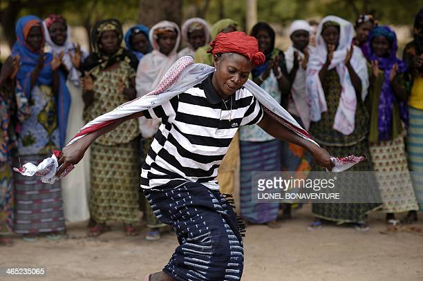 A woman dances after using traditional methods to make shea butter in Leo southcentral Burkina Faso on January 24 2014 French cosmetics company...