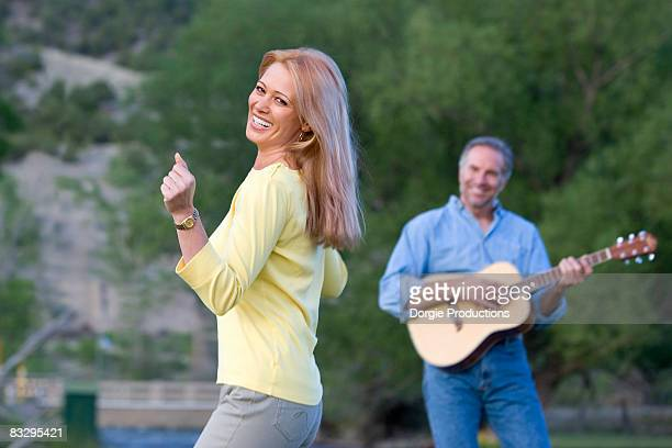 woman dances as man plays guitar - plucking an instrument stock pictures, royalty-free photos & images