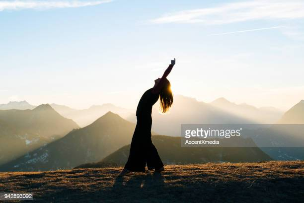 woman dances at sunrise in the mountains - mindfulness stock pictures, royalty-free photos & images