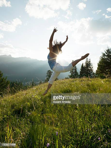 Woman dances in mountain meadow, sunrise