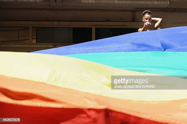 A woman dances near a Rainbow flag while taking part in the Gay Pride homosexual bisexual and transgender visibility march on June 14 in Nantes...