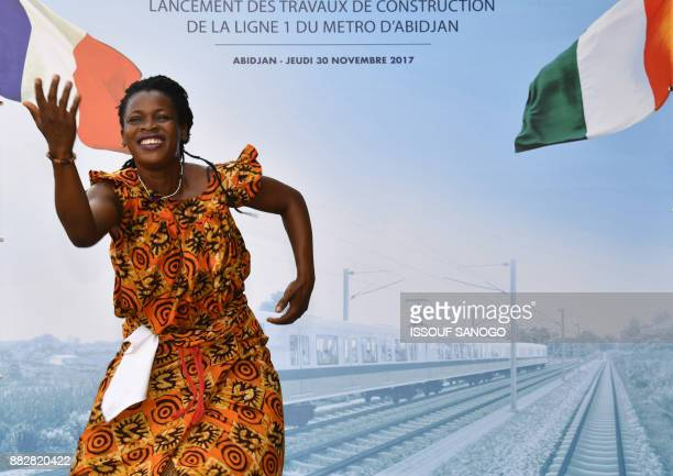 A woman dances next to poster at Treichville Train Station in Abidjan on November 30 during the inauguration ceremony of a new metro line in Abidjan...