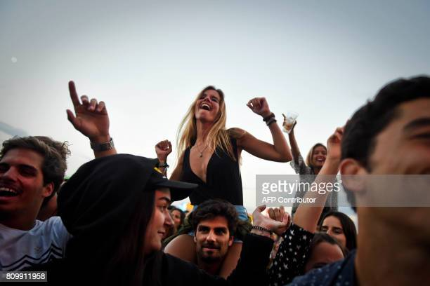 Woman dances on shoulders of a man during the 11th Alive Festival in Oeiras, near Lisbon on July 6, 2017. / AFP PHOTO / PATRICIA DE MELO MOREIRA