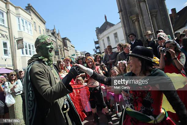 A woman dances with a man painted green as she takes part in a Beltane May Day celebration in Glastonbury main street on May 1 2013 in Glastonbury...
