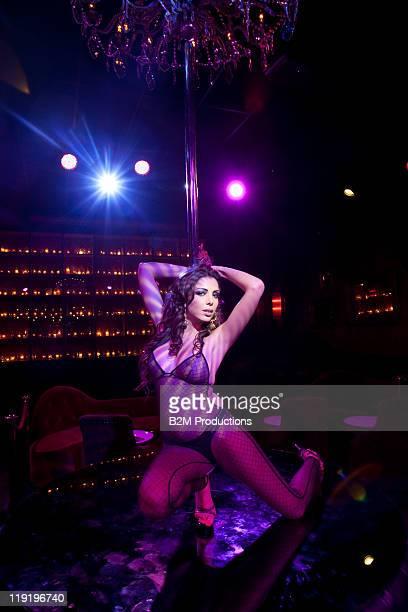 Woman dancing against a pole in nightclub