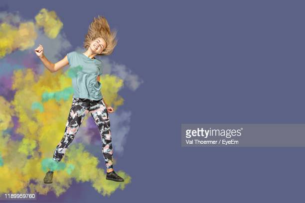 woman dancing against colored background - val thoermer stock-fotos und bilder