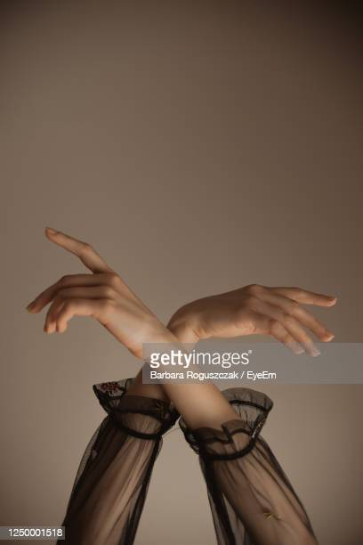 woman dancing against gray background - long sleeved stock pictures, royalty-free photos & images