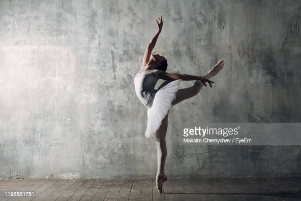 woman dancing against gray wall - ballet dancing stock pictures, royalty-free photos & images