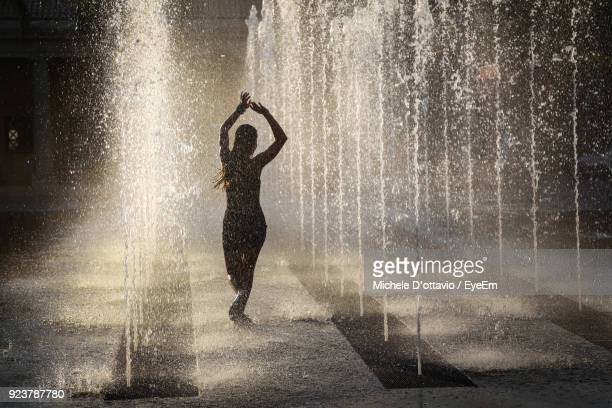 woman dancing amidst fountain - fountain stock pictures, royalty-free photos & images