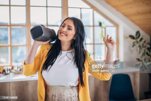 ワイヤレススピーカーを持ちながら自宅で踊る女性 - ブルートゥース ストックフォトと画像