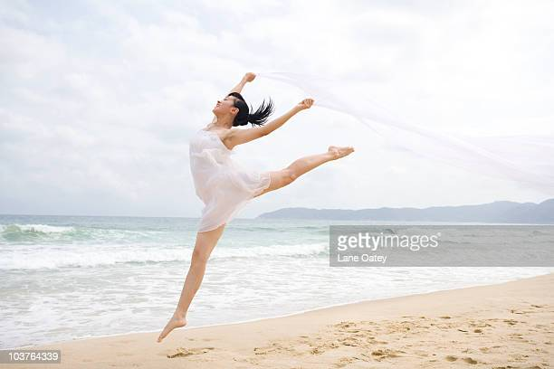a woman dancing at the beach - 白い服 ストックフォトと画像