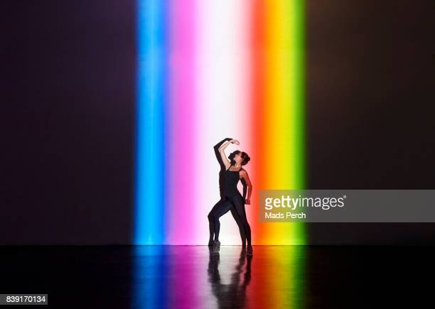 Woman dancing in dark space with splash of colours hitting the wall behind her