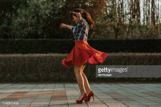 woman dancing in the city street on a sunny summer day - skirt stock pictures, royalty-free photos & images