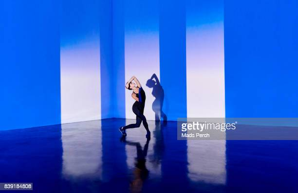 woman dancing in warehouse space with graphic projection - entertainment occupation stock pictures, royalty-free photos & images
