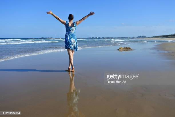 woman dancing on a beach - rafael ben ari stock-fotos und bilder