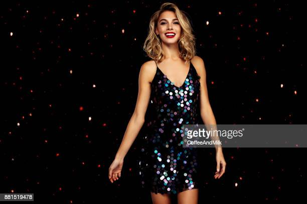 woman dancing on a party over black background with confetti - evening gown stock photos and pictures