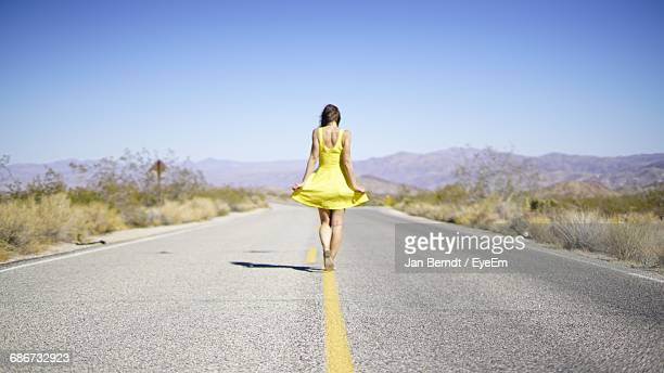 woman dancing on country road - yellow dress stock pictures, royalty-free photos & images