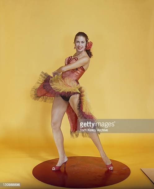 Woman dancing on round platform against yellow background