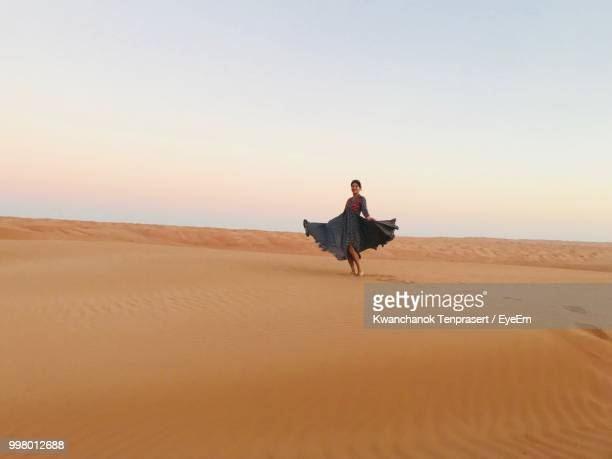 Woman Dancing On Sand At Desert Against Sky During Sunset