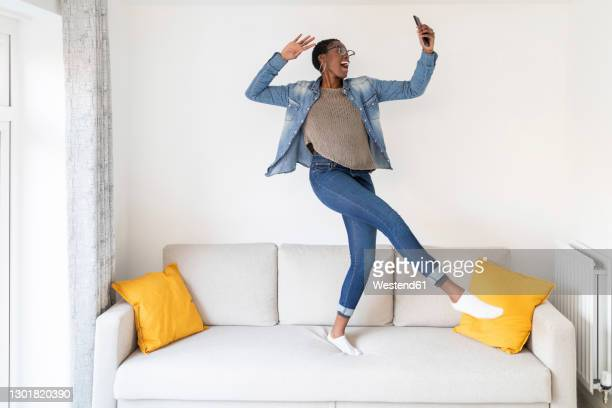 woman dancing on sofa - dancer stock pictures, royalty-free photos & images