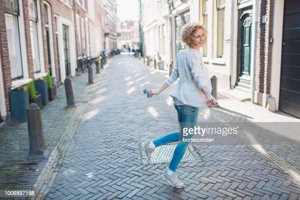 woman dancing on street in city - bortes stockfoto's en -beelden