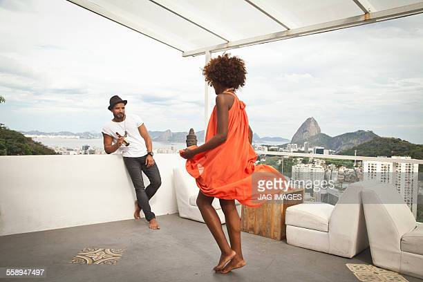 Woman dancing on terrace, Sugarloaf Mountain in background, Rio, Brazil