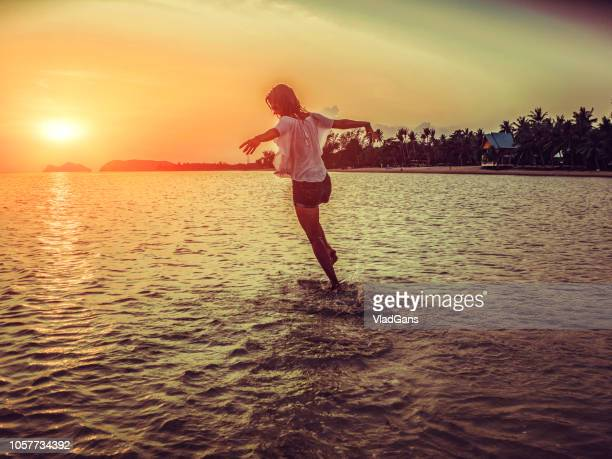 woman dancing on the beach - long dress stock pictures, royalty-free photos & images