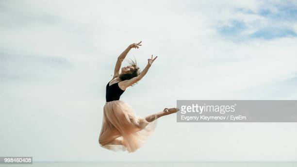 Woman Dancing Over Sea Against Sky