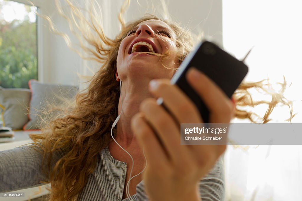 Woman dancing to music on smartphone : Stock-Foto