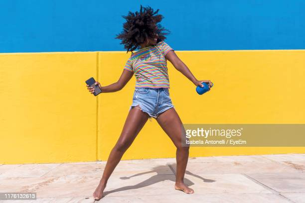 woman dancing while standing against wall - casual clothing photos et images de collection