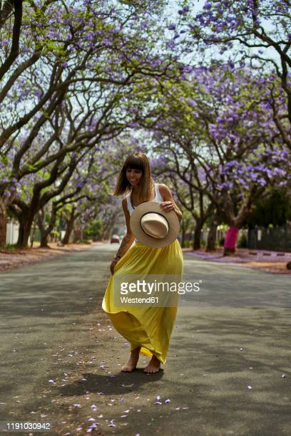 woman dancing with a hat on her hands in the middle of a street full of jacaranda trees in bloom pretoria, south africa - jacaranda ストックフォトと画像