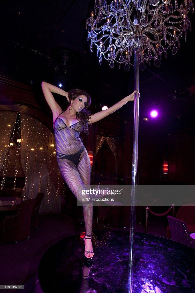 Woman dancing with a pole in nightclub : Stock Photo
