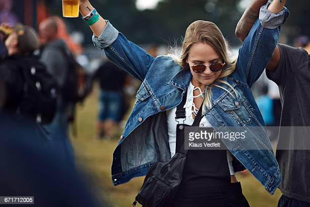Woman dancing with beer in hand at concert