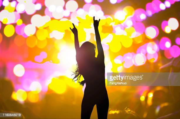 woman dancing with hands raised at night club concert - pop music stock pictures, royalty-free photos & images