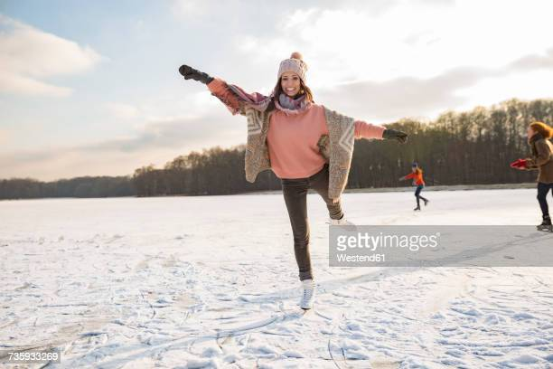 woman dancing with ice skates on frozen lake with friends - patinar - fotografias e filmes do acervo