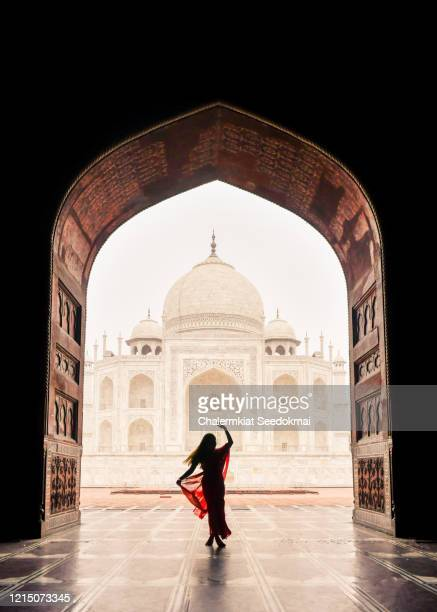 a woman dancing with the view of taj mahal in agra, india - history stock pictures, royalty-free photos & images