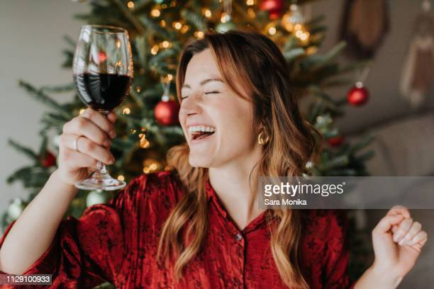 woman dancing with wine beside decorated christmas tree - drunk woman stock pictures, royalty-free photos & images