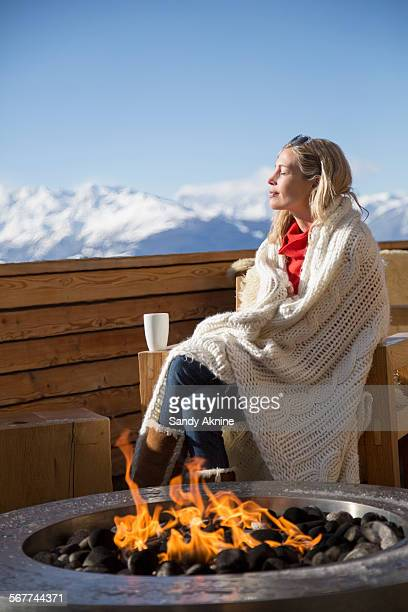 Woman day dreaming at the terrace of a hotel, Crans-Montana, Swiss Alps, Switzerland