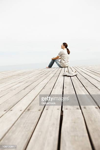woman day dreaming while sitting on a pier - pier stockfoto's en -beelden