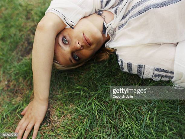 Woman daydreaming while lying on grass