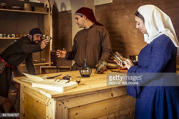 Woman debating the purchase of glasses at the apothecary run by Diotaiuti di Cecco Imola Italy mid14th century Historical reenactment